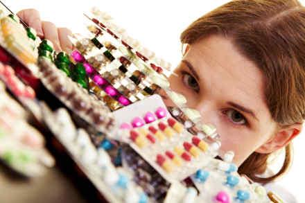 Medizinerin sitzt hinter vielen bunten Pillen